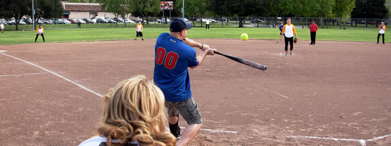 umpire view of a man playing softball who has just hit the ball with his bat